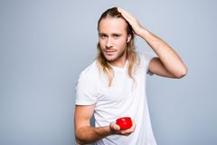 Portrait of confident happy smiling young guy with bristle, he i. S holding red jar with gel and applying gel on his long blonde clean hair, isolated on grey Royalty Free Stock Images