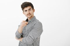 Portrait of confident joyful male enterpreneour with moustache, pointing at camera and lifting eyebrow, inviting person. Go to bar together, standing over gray royalty free stock images