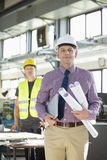 Portrait of confident male architect holding blueprints and laptop with worker in background at industry.  Royalty Free Stock Photo