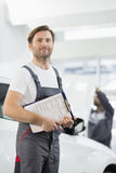 Portrait of confident male automobile mechanic with clipboard in car repair store Stock Photography