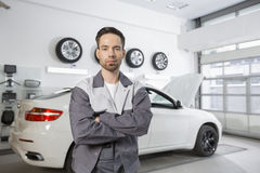Portrait of confident male automobile mechanic standing in front of car at workshop royalty free stock images