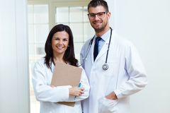 Confident male doctor and his nurse looking at camera in the office. Portrait of confident male doctor and his nurse looking at camera in the office Stock Photo
