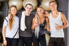 Male And Female Workout Friends Standing Together In Gym. Portrait of confident male and female friends standing together in fitness gym. Workout team Stock Photo