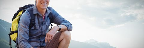 Composite image of portrait of confident male hiker crouching. Portrait of confident male hiker crouching against couple boating on a river Royalty Free Stock Photos