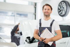 Portrait of confident male maintenance engineer with clipboard in car repair shop Stock Image