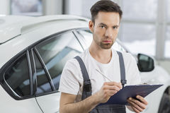Portrait of confident male maintenance engineer writing on clipboard in workshop Royalty Free Stock Photography