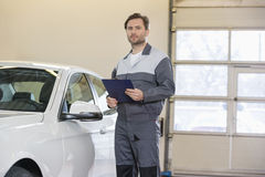 Portrait of confident male mechanic with clipboard standing by car in workshop Royalty Free Stock Images