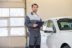 Portrait of confident male mechanic with clipboard standing by car in workshop Stock Images
