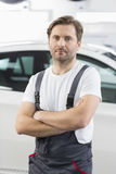Portrait of confident male mechanic standing arms crossed in workshop Stock Photo