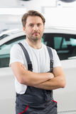 Portrait of confident male mechanic standing arms crossed in workshop Royalty Free Stock Image