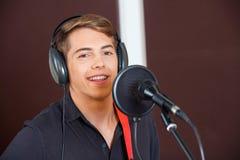 Portrait Of Confident Male Singer Performing In. Recording studio Stock Photos