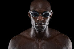 Portrait of confident male swimmer. Looking at camera against black background. Close-up image of muscular young man wearing swimming goggles Stock Photo