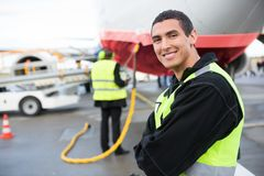 Confident Male Worker Smiling While Airplane Being Charged At Ru. Portrait of confident male worker smiling while airplane being charged at runway stock photography