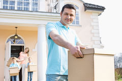 Portrait of confident man carrying cardboard box while moving house with family in background Royalty Free Stock Images