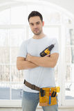 Portrait of confident man with hand drill in new house Royalty Free Stock Image