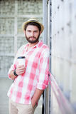 Portrait of confident man holding disposable cup while leaning on wall Stock Photo