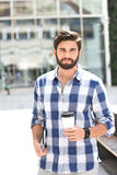 Portrait of confident man looking away while holding disposable cup and tablet PC in city Royalty Free Stock Images