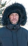 Portrait of confident man wearing fur hooded parka coat at the s Stock Image