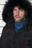Portrait of confident man wearing fur hooded parka coat at the w Stock Photography