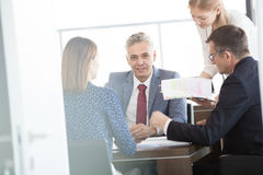 Portrait of confident mature businessman with colleagues in meeting room Royalty Free Stock Photos