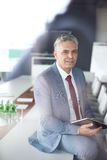 Portrait of confident mature businessman holding digital tablet while sitting on conference table Stock Photos