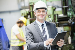 Portrait of confident mature businessman using digital tablet with worker in background at factory Royalty Free Stock Image