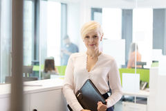 Portrait of confident mature businesswoman with file in office Stock Photos