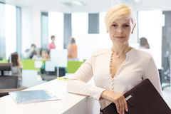 Portrait of confident mature businesswoman holding file in office Royalty Free Stock Image