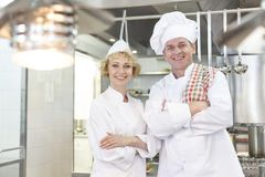Portrait of confident mature chef coworkers standing with arms crossed in kitchen at restaurant royalty free stock images