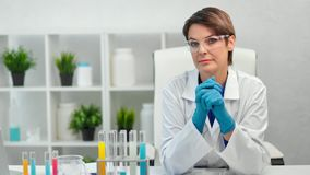 Portrait of confident mature female medical scientist in uniform posing looking at camera. Medium shot. Focused woman professional chemist in protective glasses stock video footage