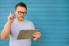 Portrait of a confident mature man holding tablet computer and pointing finger up stock image