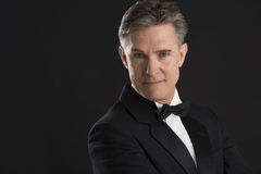 Portrait Of Confident Mature Man In Tuxedo. Isolated on black background Royalty Free Stock Image