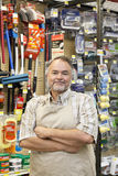 Portrait of a confident mature store clerk with arms crossed in hardware shop royalty free stock photo