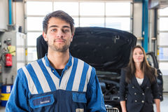 Portrait of a confident mechanic in a garage. Portrait of a young, professional, and confident mechanic, posing in front of a customer and her car with an open Stock Photography