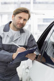 Portrait of confident mechanic holding clipboard while leaning on car's window in workshop Stock Photography