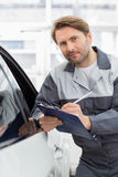 Portrait of confident mechanic holding clipboard while leaning on car's window in workshop Royalty Free Stock Photo
