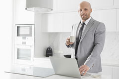 Portrait of confident mid adult businessman having coffee while using laptop in kitchen Royalty Free Stock Photos