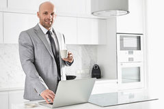 Portrait of confident mid adult businessman having coffee while using laptop in kitchen Stock Image