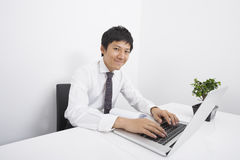 Portrait of confident mid adult businessman using laptop at office desk Stock Photos