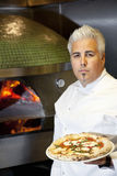 Portrait of a confident mid adult chef holding pizza Stock Photos