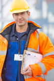 Portrait of confident mid adult man with clipboard in shipping yard Stock Photography