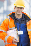 Portrait of confident mid adult man with clipboard in shipping yard Royalty Free Stock Photo