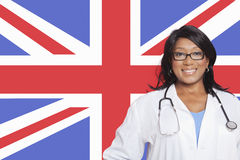 Portrait of confident mixed race female surgeon over British flag Stock Photography