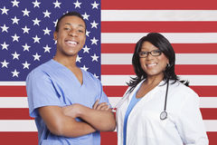 Portrait of confident mixed race male and female surgeons over American flag Stock Photo