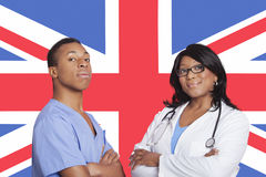 Portrait of confident mixed race male and female surgeons over British flag Stock Photos