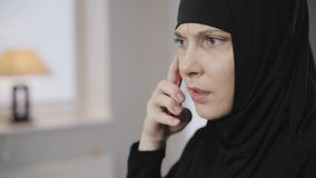 Portrait of confident muslim woman picking up phone and talking. Modern eastern lady in traditional black dress and