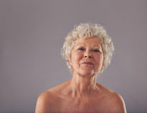 Portrait of confident old woman. Against grey background. Naked head and shoulders of senior female Stock Images