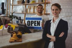 Portrait of confident owner with waiter holding open sign in cafe royalty free stock photos