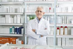 Confident Pharmacist Standing Arms Crossed In Pharmacy royalty free stock images