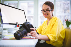 Portrait of confident photographer with camera at creative office Stock Photography